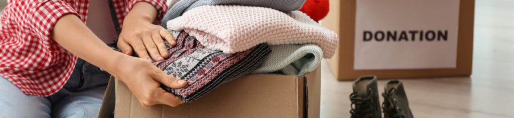 someone packing clothes into a box for donation