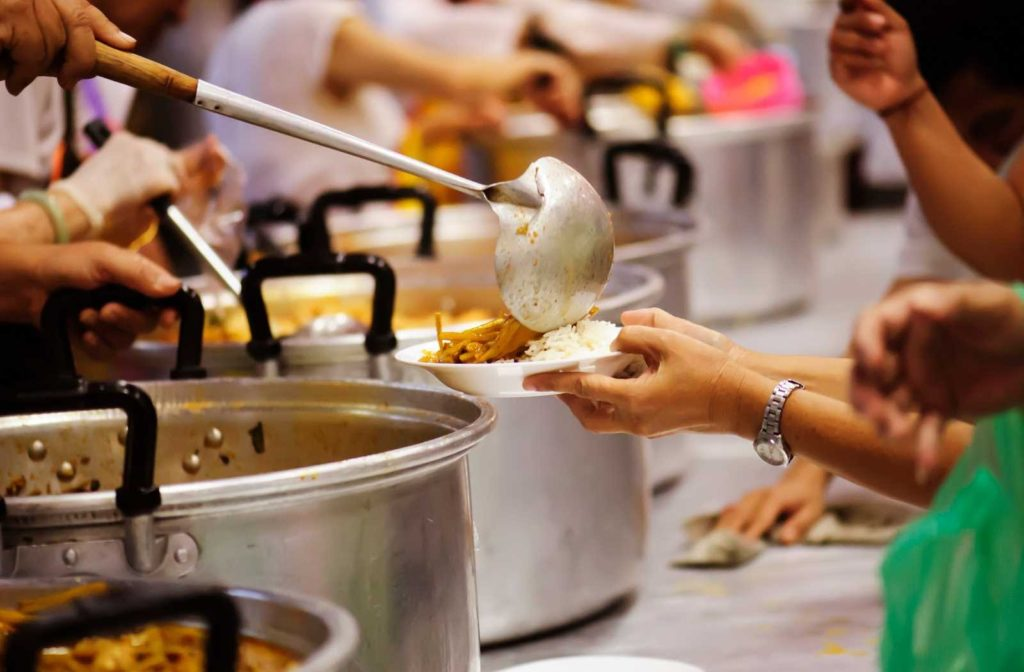 Deep focus line of pots with people ladling hot food onto plates held by woman's hands
