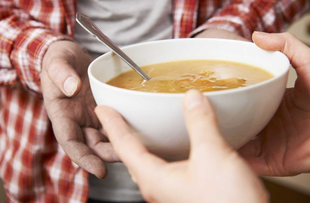 man in checkered shirt receiving a bowl of soup from volunteer's hands gratefully