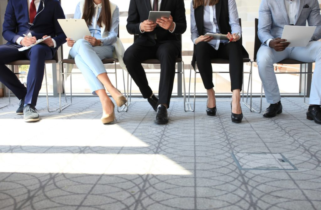 a lineup of men and women sitting in chairs holding their applications and resumes waiting for an interview