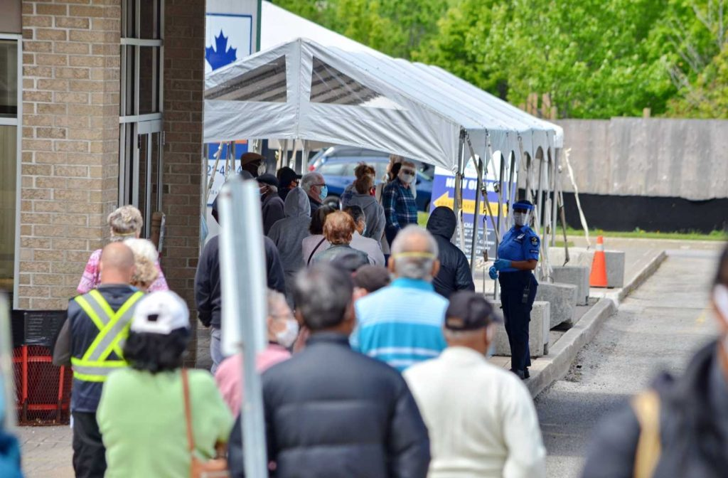 deep focus photo of Ontario lineups for covid-19 health assessments with white tent and brick building background