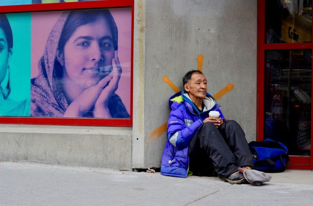 Homeless man sitting on a sidewalk with a coffee