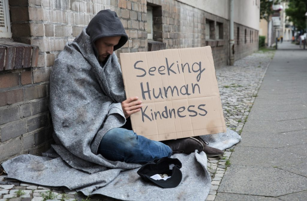 Man on street with blanket and sign that says SEEKING HUMAN KINDNESS