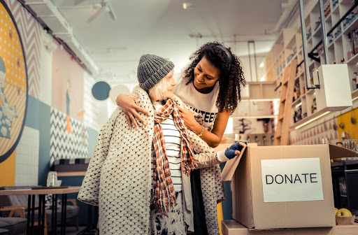 Woman helping another woman find clean clothes in donation box