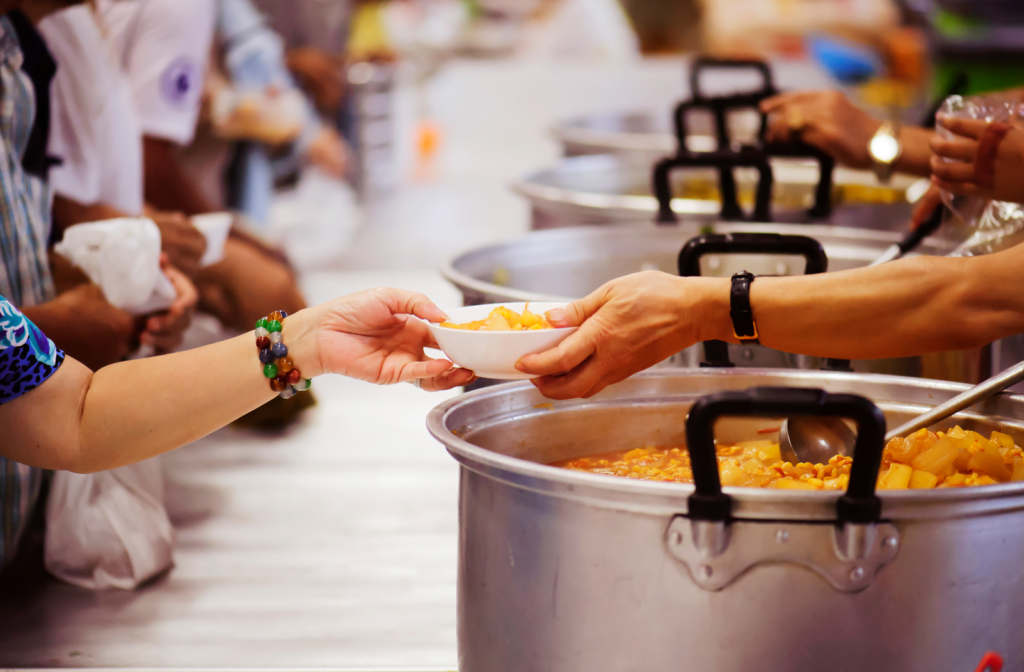 Kitchen volunteers serving meals from large pots of food