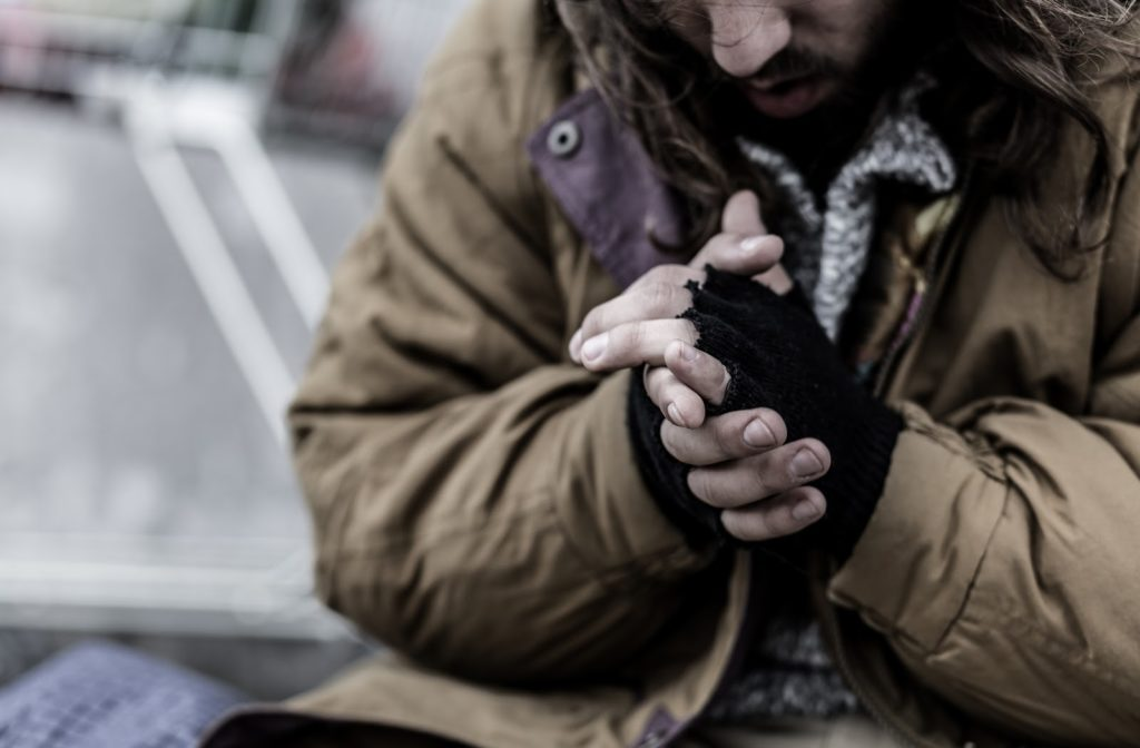 Cold homeless man wearing gloves to stay warm.