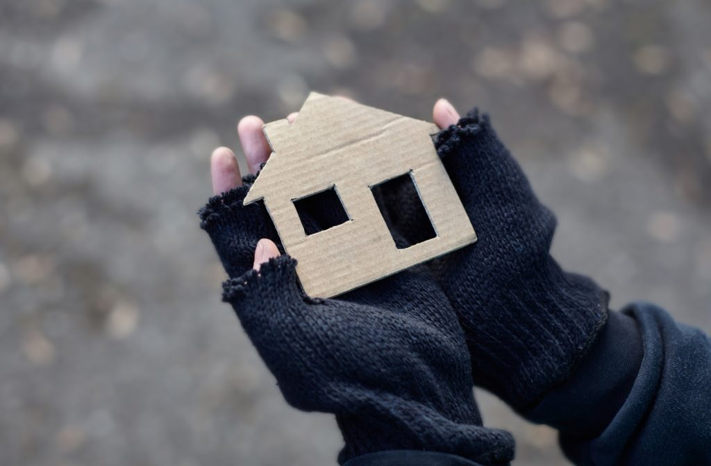 Individual holding a cardboard cut out of house in his hand while wearing gloves