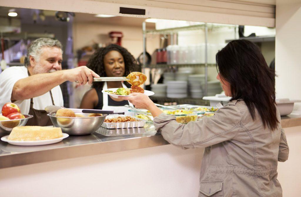 Kitchen staff serving food at homeless shelter.