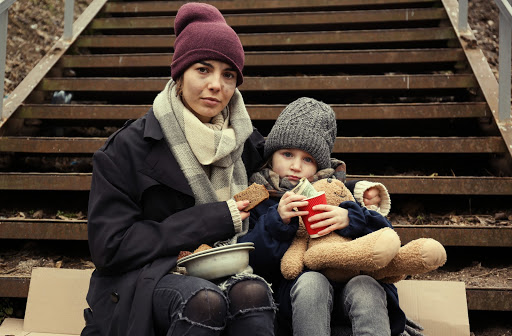 Mother and child experiencing homelessness sitting on steps while eating.