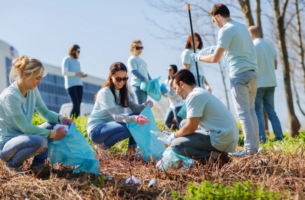 Happy volunteers helping clean the community by picking up trash on a sunny day.