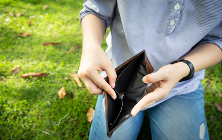 Person opening up wallet with no money inside