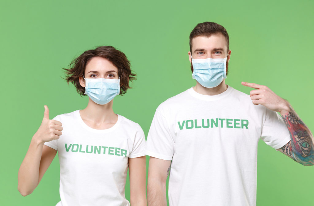 """A young man and woman wearing """"volunteer"""" shirts with their masks on"""